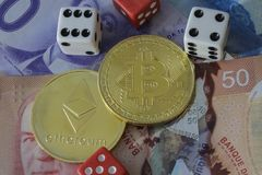 Bitcoin and etherium token with money and dice. A bitcoin and etherium token with money and dice royalty free stock photo
