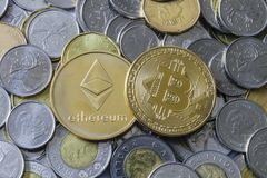 Bitcoin and Etherium Token on Money. A gold Bitcoin and Etherium Token on Canadian Coins stock photo