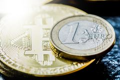 Bitcoin and Euro coin. Virtual currency Bitcoin and Euro coin on dark table Stock Photo