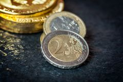 Bitcoin and Euro coin. Virtual currency Bitcoin and Euro coin on dark table Stock Image