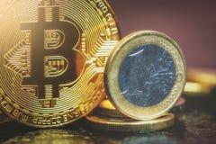 Bitcoin and Euro coin. Virtual currency Bitcoin and Euro coin on dark table Stock Photo