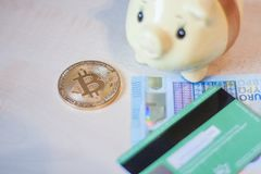 Bitcoin, euros and a credit card. A golden bitcoin, some metal and paper euros, piggy bank and a green credit card royalty free stock images