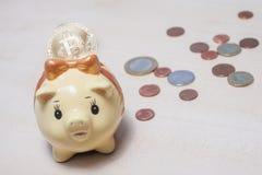 Bitcoin, euros and a piggy bank. Bitcoin, some euro coins and a small yellow piggy bank Stock Image