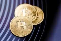 Bitcoin f?r tre guld- mynt p? en svart bakgrund arkivfoton