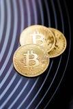 Bitcoin f?r tre guld- mynt p? en svart bakgrund royaltyfri foto