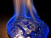 Bitcoin on fire. Real coin is burning with blue flame as symbol of hot price or critical fall. Bitcoin metal silver coin is burning with blue flame. It means hot Stock Images