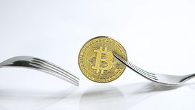 Static shot of Bitcoin fork concept with fork sliding away on the white background with reflection