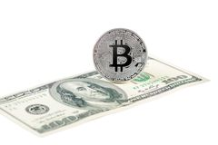 Bitcoin in front of one hundred dollar bill Royalty Free Stock Images