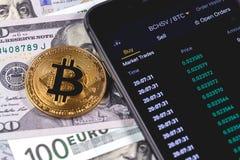 Bitcoin, geld en smartphone met cryptocurrencyeffectenbeurs stock foto's