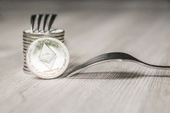 Ethereum getting New Hard Fork Change, Physical silver Crytocurrency Coin with fork, Blockchain concept stock photography