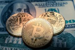Bitcoin. Gold Bitcoins on a one hundred dollar bill close up. Gold Bitcoins on a one hundred dollar bill close up Stock Photography