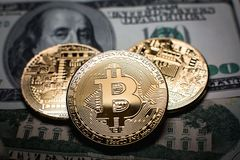 Bitcoin. Gold Bitcoins on a one hundred dollar bill close up. Gold Bitcoins on a one hundred dollar bill close up Royalty Free Stock Photography