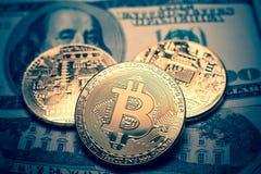 Bitcoin. Gold Bitcoins on a one hundred dollar bill close up. Gold Bitcoins on a one hundred dollar bill close up Royalty Free Stock Photos