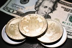 Bitcoin. Gold Bitcoins on a one hundred dollar bill close up. Gold Bitcoins on a one hundred dollar bill close up Stock Images