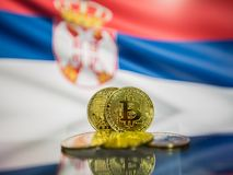 Bitcoin gold coin and defocused flag of Serbia background. Virtual cryptocurrency concept. stock photo