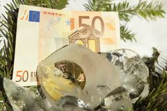Bitcoin gold coin frozen in half in a piece of ice on a white background with Christmas tree branches and 50 euro of Europe. Image stock photography