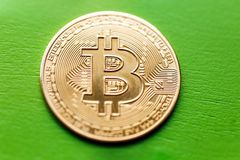 Bitcoin gold coin on a green wooden background stock images