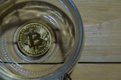 Bitcoin gold in a jar on wooden table background. Savings or business concept. N royalty free stock photo