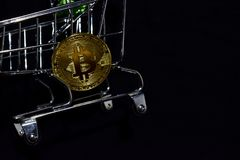 Bitcoin gold and shopping cart on black background. Bitcoin outside a shopping cart. Business concept royalty free stock images