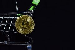 Bitcoin gold and shopping cart on black background. Bitcoin outside a shopping cart. Business concept. N royalty free stock photography