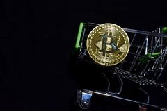 Bitcoin gold and shopping cart on black background. Bitcoin outside a shopping cart. Business concept. N royalty free stock photos