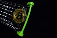 Bitcoin gold in a shopping cart on black background. Buy and sell Business concept. N stock photography