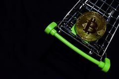 Bitcoin gold in a shopping cart on black background. Buy and sell Business concept. N stock images
