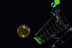Bitcoin gold and shopping cart on black background. Bitcoin falls from a shopping cart concept royalty free stock image