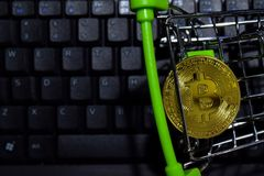 Bitcoin gold in Shopping cart on keyboard laptop background. Trade and business concept. N royalty free stock photography