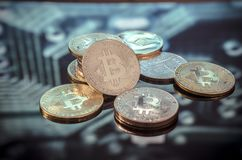 Bitcoin gold, silver and copper coins and defocused printed circ stock images