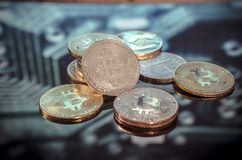 Bitcoin gold, silver and copper coins and defocused printed circ royalty free stock photo