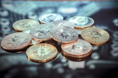 Bitcoin gold, silver and copper coins and defocused printed circ royalty free stock image