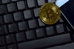 Bitcoin gold and smartphone on keyboard laptop background. Trade and business concept royalty free stock images