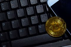 Bitcoin gold and smartphone on keyboard laptop background. Trade and business concept. N stock image