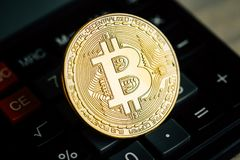 Bitcoin golden coin on calculator keyboard.  Virtual cryptocurrency concept Stock Images