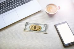 Bitcoin golden coins on a dollar banknotes. Office background. Cup of coffee, white laptop, mobile phone, and money. Money balance Stock Photo