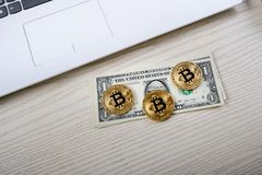 Bitcoin golden coins on a table with dollar banknotes and laptop. Virtual money. Cryptocurrency business. Office background. Stock Photography