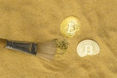 Bitcoin on golden sand. An archaeologist with a brush clears the bitcoin coin on the golden sand. top view. finding and mining cryptocurrency stock photography