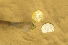 Bitcoin on golden sand. An archaeologist with a brush clears the bitcoin coin on the golden sand. top view. finding and mining cryptocurrency royalty free stock image