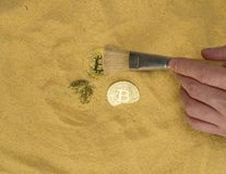 Bitcoin on golden sand. An archaeologist with a brush clears the bitcoin coin on the golden sand. top view. finding and mining cryptocurrency royalty free stock images