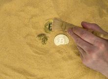 Bitcoin on golden sand. An archaeologist with a brush clears the bitcoin coin on the golden sand. top view. finding and mining cryptocurrency royalty free stock photo