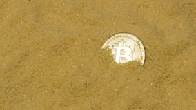 Bitcoin on golden sand. One bitcoin crypto coin on brilliant golden sand. finding and mining cryptocurrency stock photography
