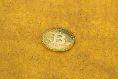 Bitcoin on golden sand. One bitcoin crypto coin on a shiny golden sand background with backlight royalty free stock photo