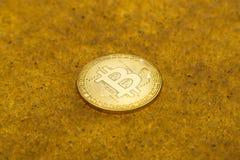 Bitcoin on golden sand. One bitcoin crypto coin on a shiny golden sand background with backlight stock photos