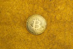 Bitcoin on golden sand. One bitcoin crypto coin on a shiny golden sand background with backlight, top view royalty free stock images