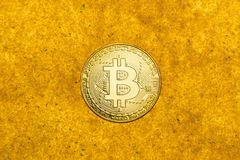 Bitcoin on golden sand. One bitcoin crypto coin on a shiny golden sand background with backlight, top view royalty free stock photo