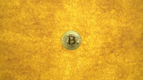 Bitcoin on golden sand. One bitcoin crypto coin on a shiny golden sand background with backlight, top view. zoom effect stock footage