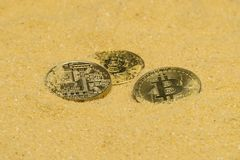 Bitcoin on golden sand. Several bitcoin crypto coins on brilliant golden sand. finding and mining cryptocurrency royalty free stock image