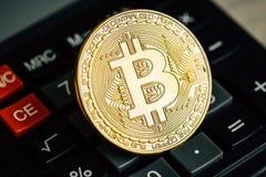 Bitcoin gouden muntstuk op calculatortoetsenbord Virtueel cryptocurrencyconcept Stock Foto's