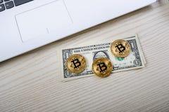 Bitcoin gouden muntstukken op een lijst met dollarbankbiljetten en laptop Virtueel Geld Cryptocurrencyzaken Bureauachtergrond Stock Fotografie